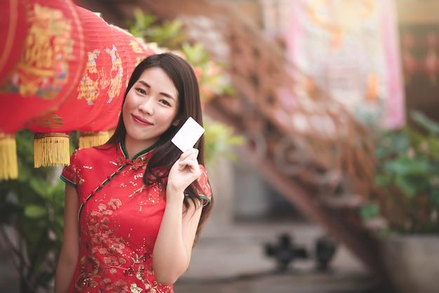 Donna asiatica in vestito rosso che tiene credito in bianco per la compera nel festival cinese di nuovo anno