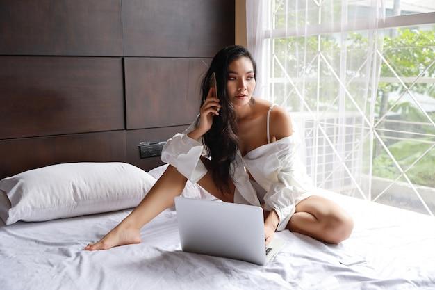 Donna asiatica indipendente adulta in camicia bianca che lavora al computer e telefono cellulare in camera da letto con il fronte di bellezza