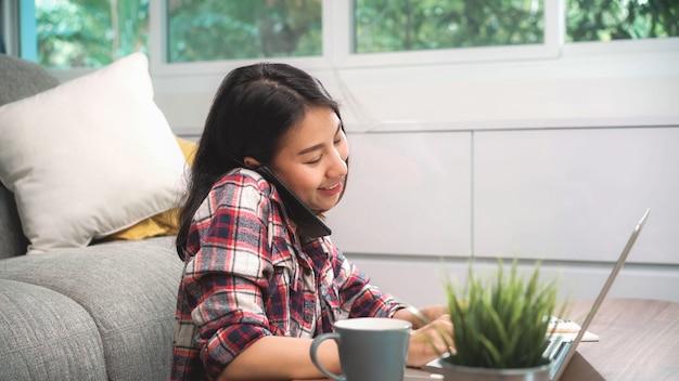 Donna asiatica indipendente che lavora a casa, femmina che lavora al computer portatile e che utilizza telefono cellulare che parla con il cliente sul sofà in salone a casa.