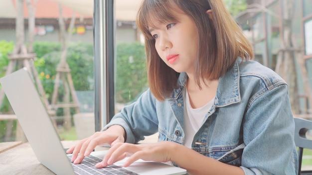 Donna asiatica indipendente di affari che lavora, facendo progetti e inviando email sul computer portatile o sul computer mentre sedendosi sulla tavola in caffè.