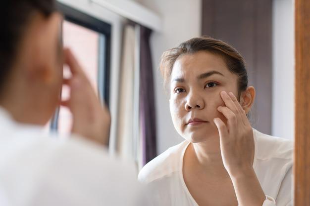 Donna asiatica invecchiata centrale che esamina le grinze in specchio