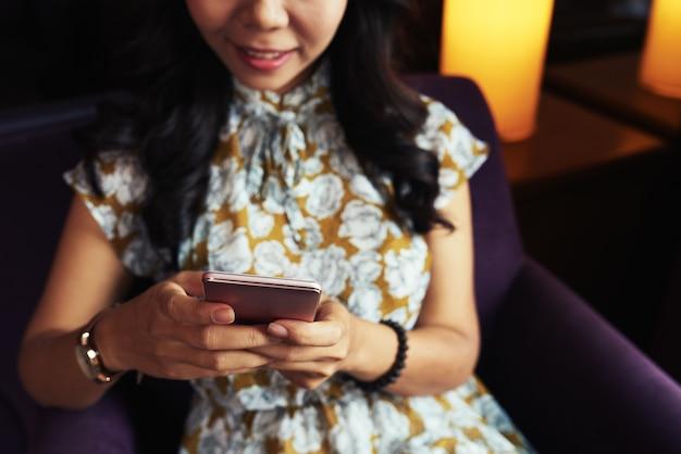 Donna asiatica irriconoscibile che si siede in poltrona e che per mezzo dello smartphone