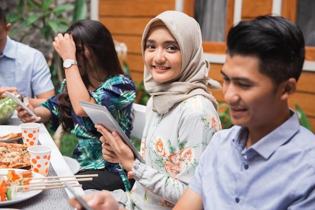 Donna asiatica musulmana che usando linguetta mentre con gli amici