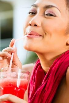 Donna asiatica nel bere al ristorante