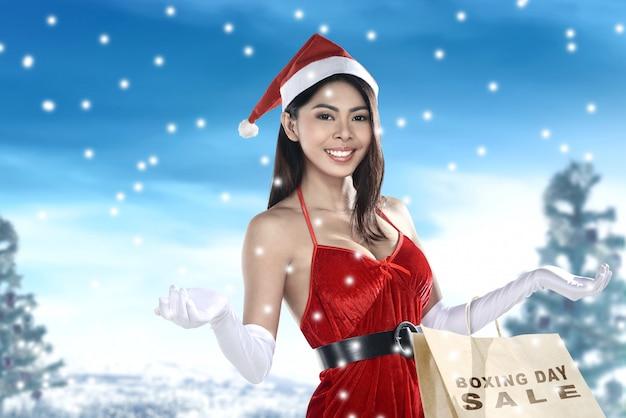 Donna asiatica nel sacchetto della spesa della tenuta del costume di santa con la vendita di santo stefano