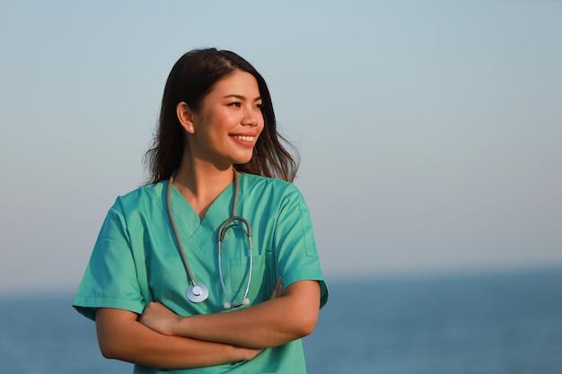 Donna asiatica nel sorriso del ritratto dell'uniforme di medico e fronte felice