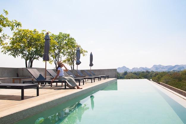 Donna asiatica rilassante in piscina sul tetto
