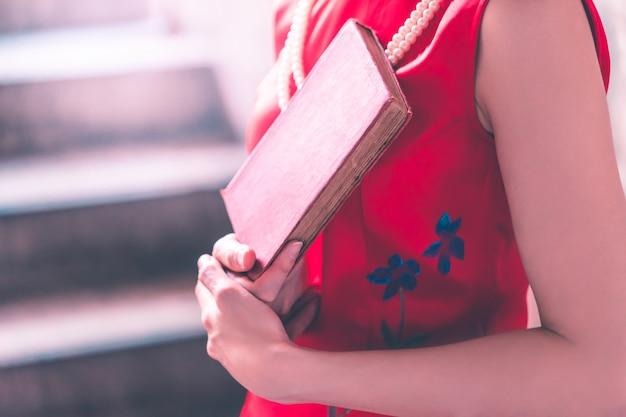 Donna asiatica rossa che tiene un libro rosso in sua mano