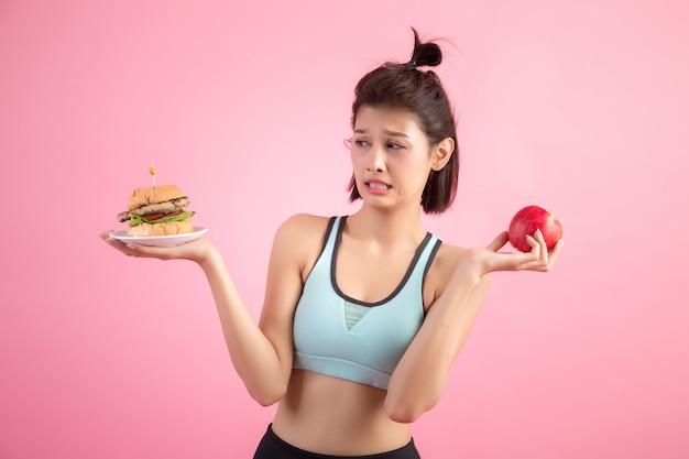 Donna asiatica scegliendo tra hamburger e mela rossa sul rosa