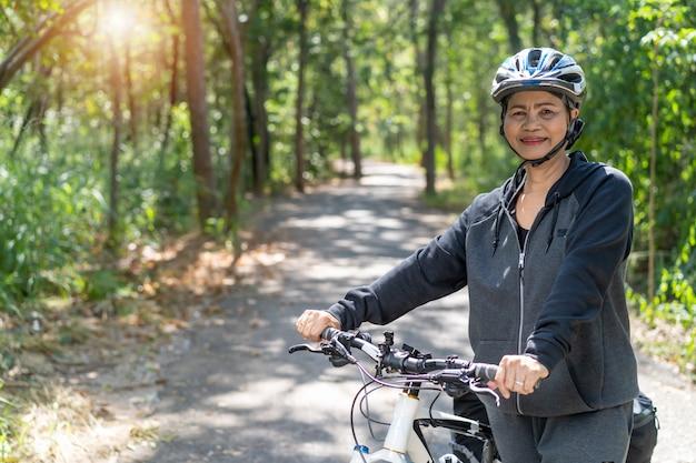Donna asiatica senior attraente con la bicicletta in parco