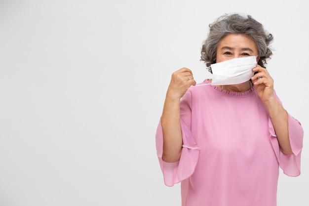 Donna asiatica senior che indossa una maschera protettiva per la peste coronavirus o malattia infettiva covid-19. maschera igienica facciale per consapevolezza ambientale di sicurezza esterna o concetto di diffusione del virus