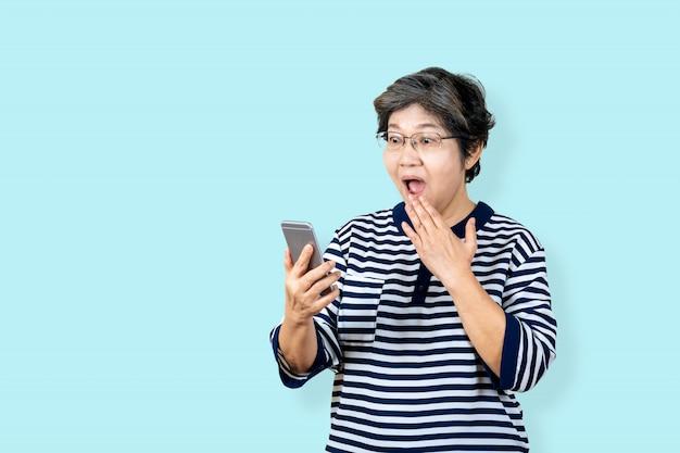 Donna asiatica senior sorpresa che tiene e che guarda smartphone sul fondo isolato che ritiene sorpreso e stupito. fondo femminile dell'azzurro di stile di vita femminile più anziano.