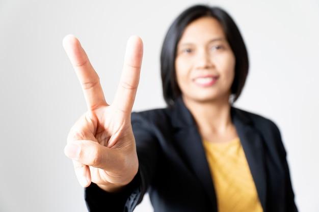 Donna asiatica sicura di affari del ritratto che presenta mano su bianco