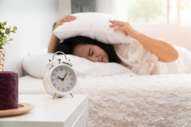 Donna asiatica sonnolenta che dorme sul letto e usa un cuscino per chiudere l'orecchio in modo da non sentire la sveglia in camera da letto.