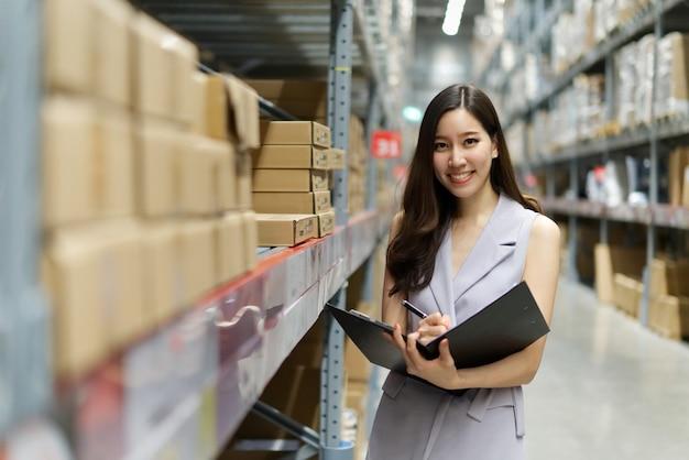 Donna asiatica sorridente astuta che lavora nel magazzino del deposito.