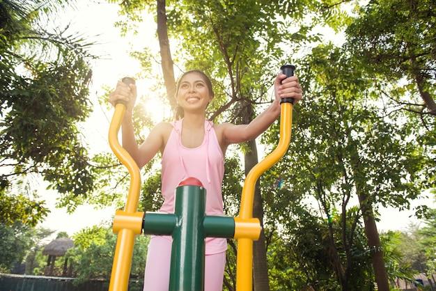 Donna asiatica sorridente che fa allenamento sulla macchina ellittica