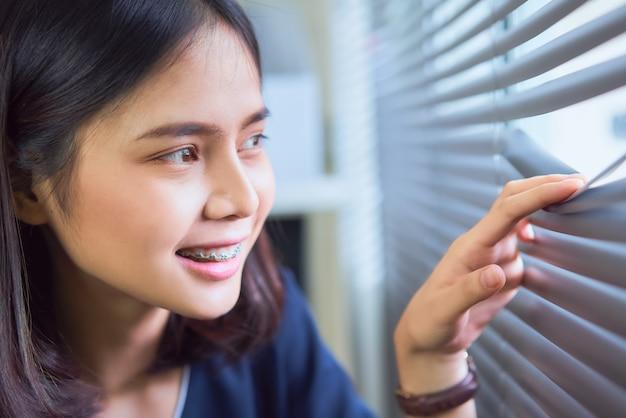 Donna asiatica sorridente che guarda dalla finestra dell'ufficio.