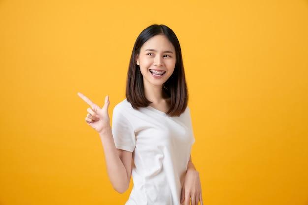 Donna asiatica sorridente che indica dito su fondo giallo