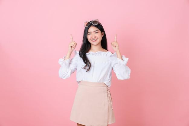 Donna asiatica sorridente che indica dito su fondo rosa
