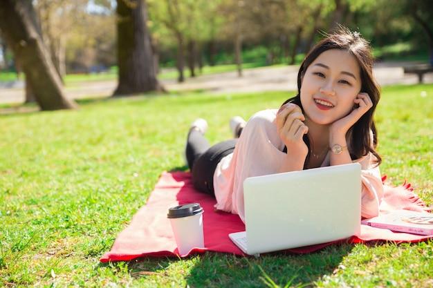 Donna asiatica sorridente che mangia mela e che utilizza computer portatile sul prato inglese