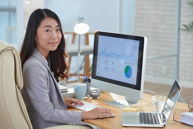 Donna asiatica sorridente che si siede allo scrittorio in ufficio e che lavora al rapporto finanziario