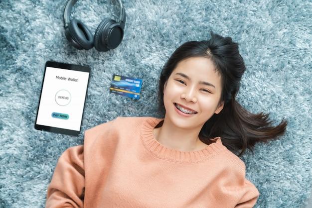 Donna asiatica sorridente che si trova sul pavimento