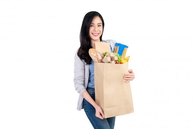 Donna asiatica sorridente che tiene il sacchetto della spesa di carta pieno di verdure e generi alimentari