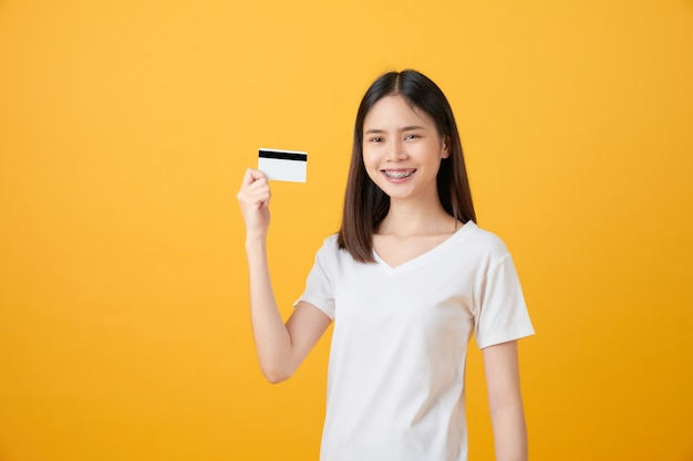 Donna asiatica sorridente che tiene una carta di credito