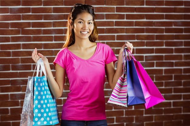 Donna asiatica sorridente con i sacchetti della spesa sul muro di mattoni