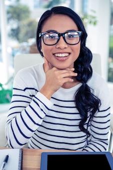 Donna asiatica sorridente con la mano sul mento che esamina la macchina fotografica in ufficio