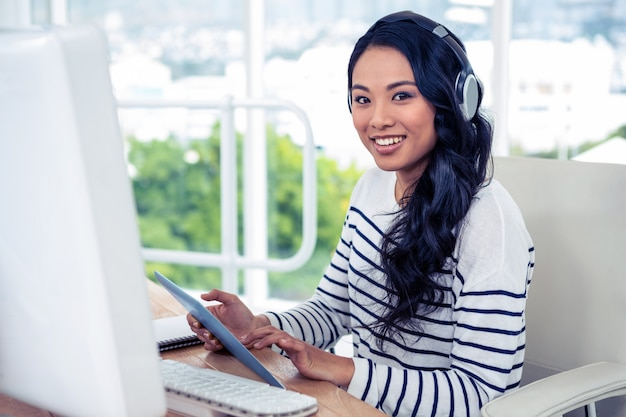 Donna asiatica sorridente con le cuffie facendo uso della compressa e di esaminare la macchina fotografica in ufficio
