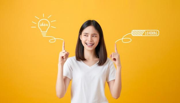 Donna asiatica sorridente dei giovani che indica le mani la lampadina con le idee del testo e lampo di genio di caricamento su fondo giallo.