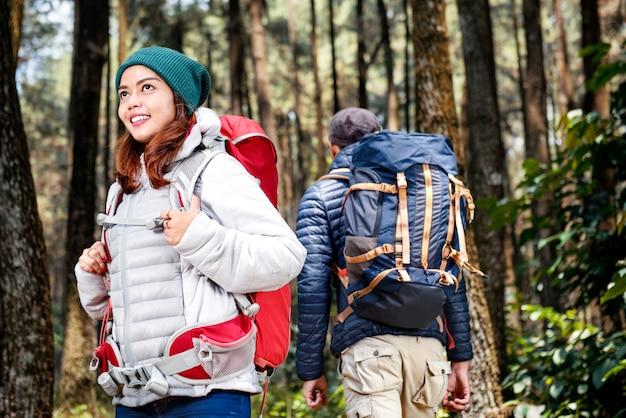 Donna asiatica sorridente delle viandanti che esplora con l'uomo delle viandanti