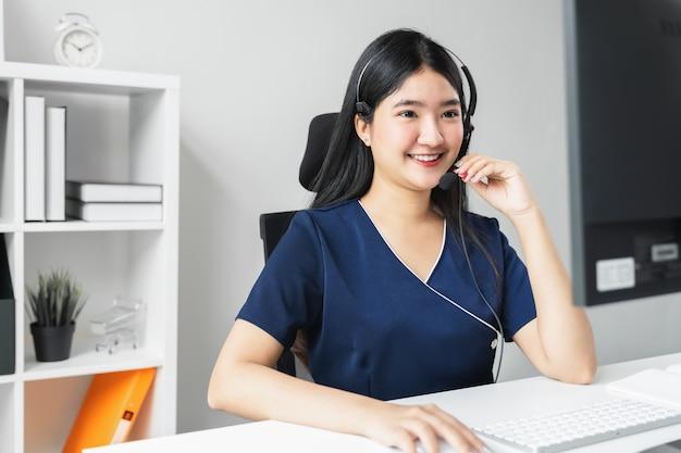 Donna asiatica sorridente di affari che lavora nella call center alla scrivania con la cuffia avricolare e il computer.