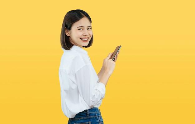 Donna asiatica sorridente felice con lo smart phone della tenuta su giallo