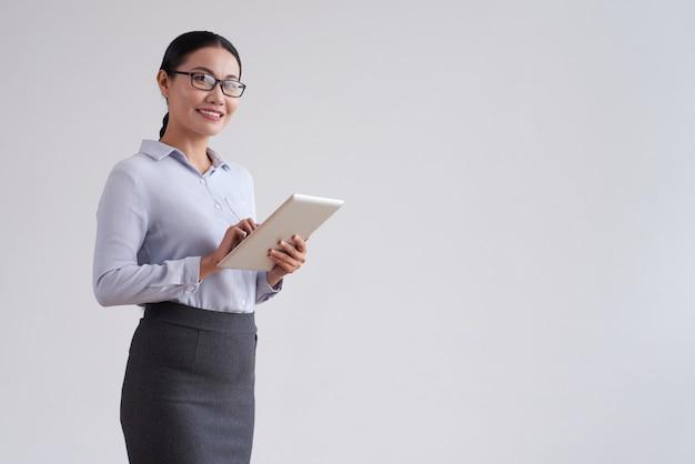 Donna asiatica sorridente in vetri che tengono il computer della compressa e che esaminano macchina fotografica