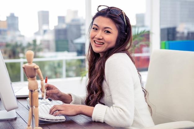 Donna asiatica sorridente sul computer che esamina la macchina fotografica in ufficio