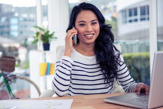 Donna asiatica sorridente sulla telefonata che esamina la macchina fotografica in ufficio