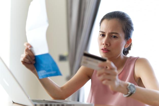 Donna asiatica stressata che tiene la carta di credito e le fatture che si preoccupano di trovare i soldi per pagare il debito della carta di credito e tutte le fatture di prestito.