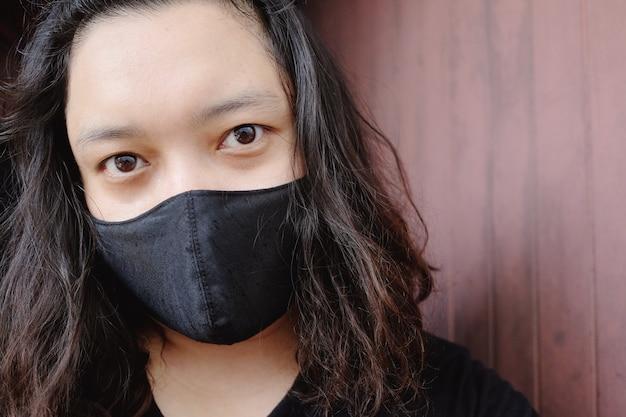 Donna asiatica thailandese che indossa una maschera di stoffa nera per prevenire il virus covid-19 o corona e la malattia epidemica