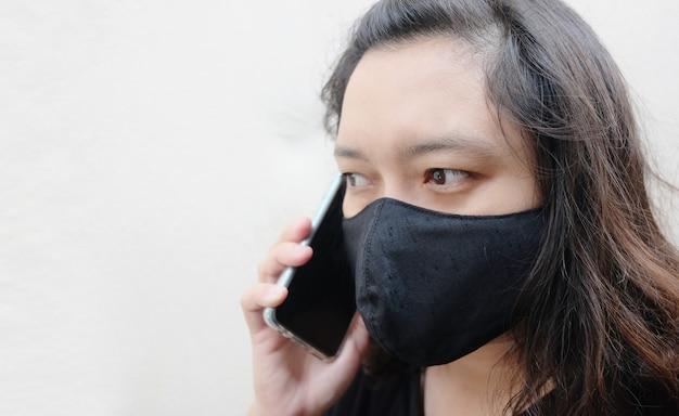 Donna asiatica thailandese che indossa una maschera di stoffa nera per prevenire il virus covid-19 o corona e parlare sullo smartphone