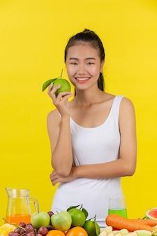 Donna asiatica tieni le arance con la mano destra e sul tavolo ci sono molti frutti.