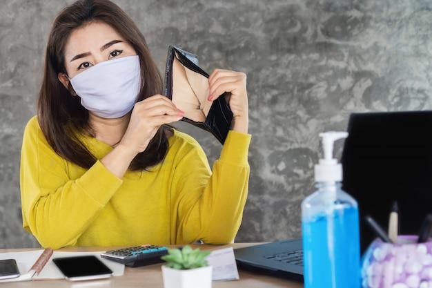 Donna asiatica triste con la maschera di protezione che ha problema finanziario