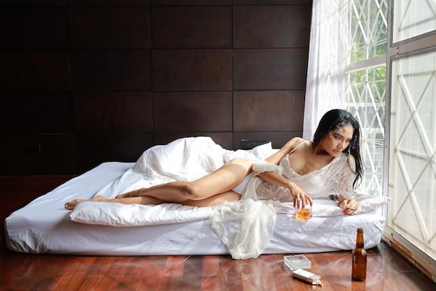 Donna asiatica ubriaca in biancheria bianca, bevendo e fumando mentre tiene la bottiglia dell'alcool del liquore e trovandosi sul letto in camera da letto