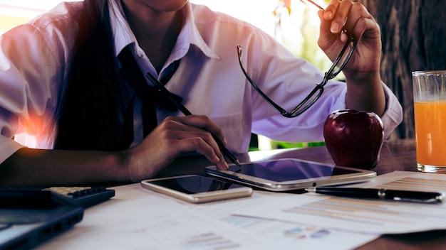 Donna asiatica utilizzando tavoletta sul tavolo in caffè con annata tonica.
