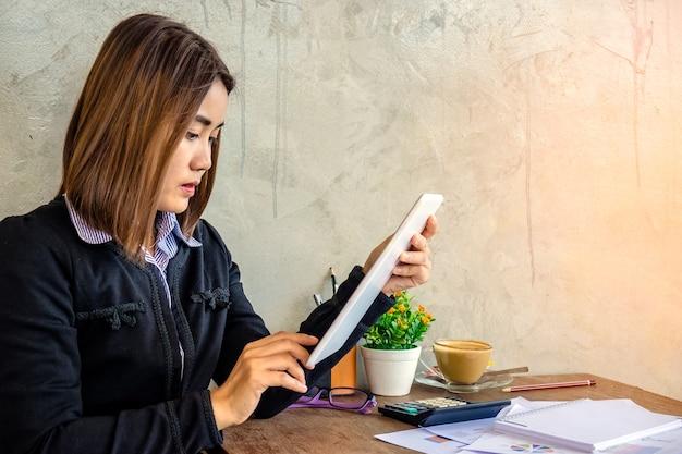 Donna asiatica utilizzando tavoletta sul tavolo in caffè