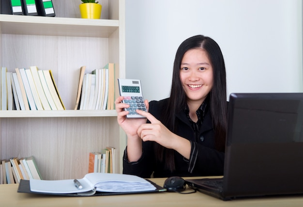 Donna astuta di affari che mostra il calcolatore in ufficio