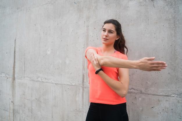 Donna atletica che allunga le gambe prima dell'esercizio.