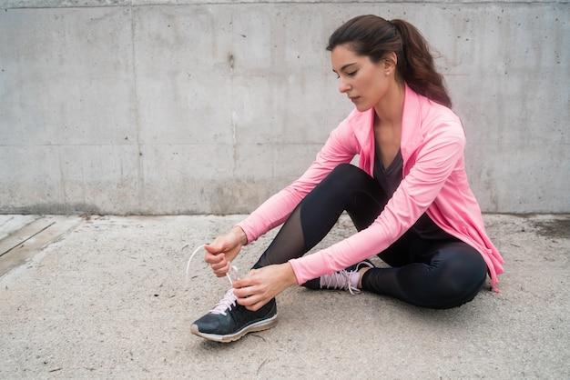 Donna atletica che lega i suoi laccetti.
