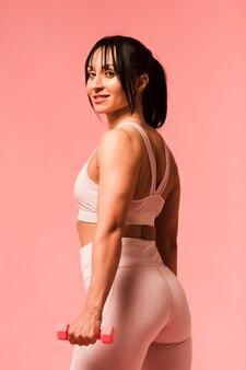 Donna atletica che posa con i pesi